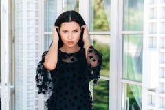Stående av ett ungt härligt svartklänning-ingrepp för flicka som M stadigt stirrar in i kameran Modellen kör långt svart hår arkivfoto