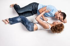 Stående av ett ungt lyckligt par som ligger på golv Fotografering för Bildbyråer