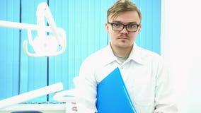 Stående av ett ungt manligt doktorsanseende i medicinskt kontor och att rymma en blå mapp under hans arm, medicinbegrepp arkivfilmer
