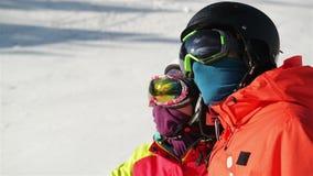 Stående av ett ungt par på den snöig semesterorten De bär Ski Goggles And Helmet stock video