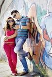 Stående av ett ungt par som ser den mobila telefonen Fotografering för Bildbyråer