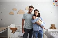 Stående av föräldrar med den nyfödda sonen i barnkammare Royaltyfria Foton