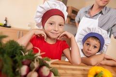 Stående av föräldrar och två barn som gör mat Arkivfoto