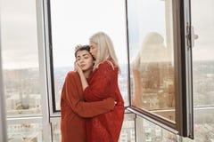 Stående av förälskad bärande röd kläder för attraktiva lesbiska par som kramar nära öppnat fönster, medan stå på balkong Arkivfoto