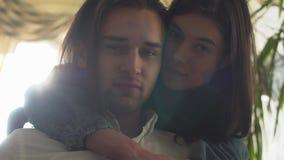 Stående av förälskade härliga omfamna par Stilig man som kysser hans flickvän med långt brunt hår och stora ögon stock video