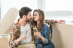 stående av förälskade klirra exponeringsglas för par av champagne på det nya huset med att flytta sig för kartonger arkivbilder