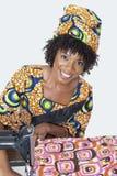 Stående av för modeformgivare för afrikansk amerikan ett kvinnligt tyg för sömnad över grå bakgrund Royaltyfri Bild