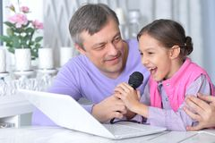 Stående av fadern med den lilla dottern som sjunger karaoke arkivfoto