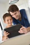 Stående av fadern och sonen som websurfing fotografering för bildbyråer