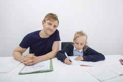 Stående av fadersammanträde med dottern som studerar på tabellen royaltyfri foto