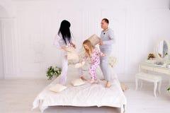 Stående av familjbanhoppningen på säng som tillsammans ser kameran in royaltyfri foto