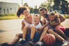 Stående av familjen med två barn på basketlekplatsen fotografering för bildbyråer