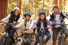 Stående av familjen som cyklar till och med nedgångskogsmark Royaltyfria Foton