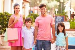 Stående av familjen som promenerar gatan med shoppingpåsar royaltyfria bilder