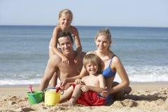 Stående av familjen som tycker om strandferie Arkivbild