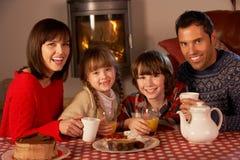 Stående av familjen som tycker om Tea och caken Arkivbild