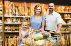 Stående av familjen som väljer bröd och sötsaker i bageriavsnitt arkivfoto