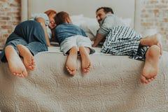 Stående av familjen tre par av fot i säng royaltyfri foto