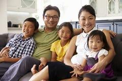 Stående av familjsammanträde på Sofa At Home Together royaltyfria bilder