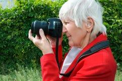 St?ende av farmodern att g?ra fotoet utomhus p? soldagen modern caucasian farmor att rymma hennes kamera henne som anv?nder photo royaltyfri fotografi