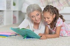 Stående av farmodern med den gulliga lilla flickan som tillsammans gör läxa, medan ligga på golv royaltyfria foton