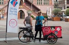 Stående av flickalyxfnasket från turisbyrå på informationsställningen med trehjulingen Arkivbild