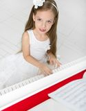 Stående av flickan i den vita klänningen som spelar pianot Arkivbild