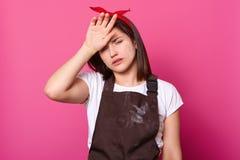 Stående av flickan i det bruna förklädet, vit t-skjorta, röd hårmusikband, med trött uttryck på rosa bakgrund Modellen poserar in royaltyfria bilder