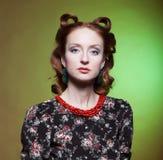 Stående av flickan i retro stil med röda pärlor. Arkivbild