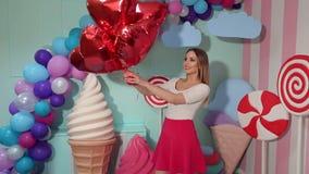 Stående av flickan med ballonger i rum med godisen