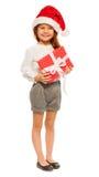 Stående av flickan med den stora gåva och jultomtenhatten royaltyfri bild