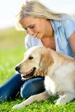 Stående av flickan med hunden på gräs arkivbild