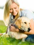 Stående av flickan med labrador på gräs arkivbild