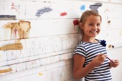 Stående av flickan mot den dolda väggen för målarfärg i Art Studio royaltyfri bild