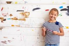 Stående av flickan mot den dolda väggen för målarfärg i Art Studio arkivfoto