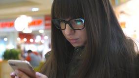 Stående av flickasammanträde i shoppinggallerian och användasmartphonen Ung kvinna i exponeringsglas som ser telefonen och lager videofilmer
