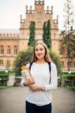 Stående av flickauniversitetsstudenten utomhus på universitetsområde arkivbilder