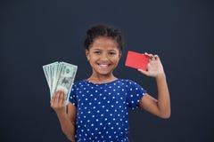 Stående av flickavisningkreditkorten och valuta Arkivfoto