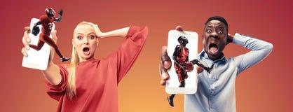 Stående av folk som visar skärmen av mobiltelefonen som isoleras över orange bakgrund fotografering för bildbyråer