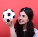 Stående av fotboll och att se för kvinna hållande den med hat a fotografering för bildbyråer