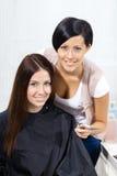 Stående av frisör- och klientsammanträde på stol royaltyfria foton