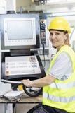 Stående av fungerande maskineri för kvinnlig arbetare på kontrollbordet i fabrik arkivfoto