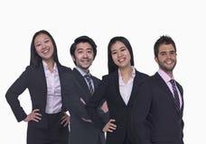 Stående av fyra unga affärspersoner som ser kameran, längd för tre fjärdedel, studioskott arkivbild