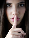 Stående av gesten för hand för tystnad för brunettflickavisning Arkivfoto