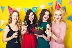 Stående av glade vänner som rostar och ser kameran på födelsedagpartiet Le flickor med exponeringsglas av champagne Royaltyfri Foto