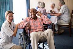 Stående av gladlynt sammanträde för hög man för handikappade personer på rullstolen med den kvinnliga doktorn royaltyfri bild