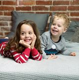 Stående av gladlynt syskon som kopplar av i sovrum arkivfoto