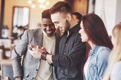 Stående av gladlynta unga vänner som ser den smarta telefonen, medan sitta i kafé Folk för blandat lopp, i att använda för restau fotografering för bildbyråer