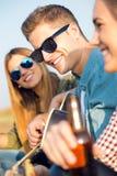 Stående av gruppen av vänner som spelar gitarren och dricker öl Royaltyfria Bilder