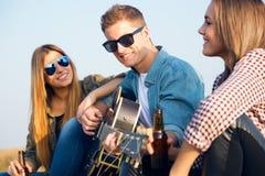 Stående av gruppen av vänner som spelar gitarren och dricker öl Arkivfoto